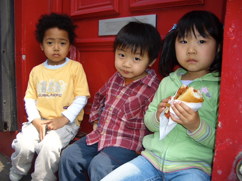 A trio of tykes enjoy street food along Notting Hill's Portobello Road.