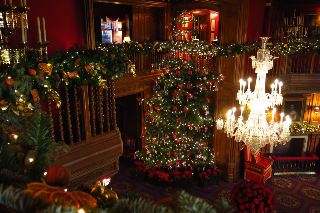 A huge Christmas tree and garlands bedeck the wood-paneled entry hall at Ashford Castle