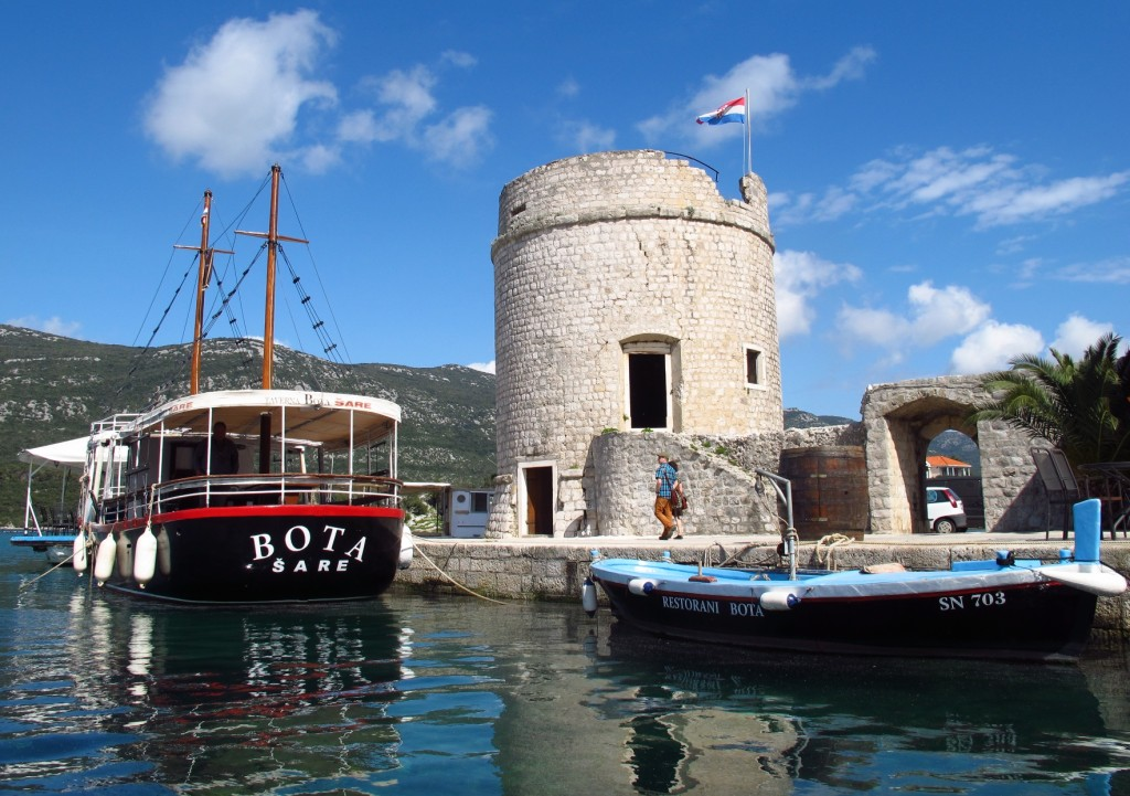 A boat berthed beside a stone tower in Ston Harbor, Croatia