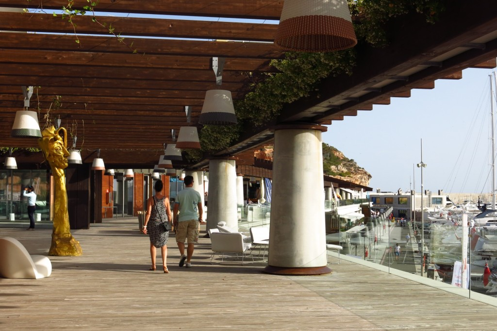 A couple holds hands as they stroll around Port Adriano, designed by Philippe Starck