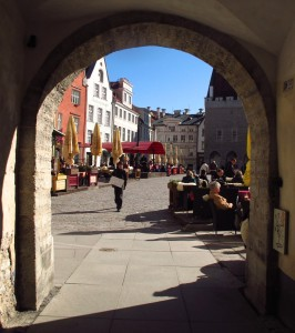 an archway frames a view of the Old Town Square in Tallinn, Estonia