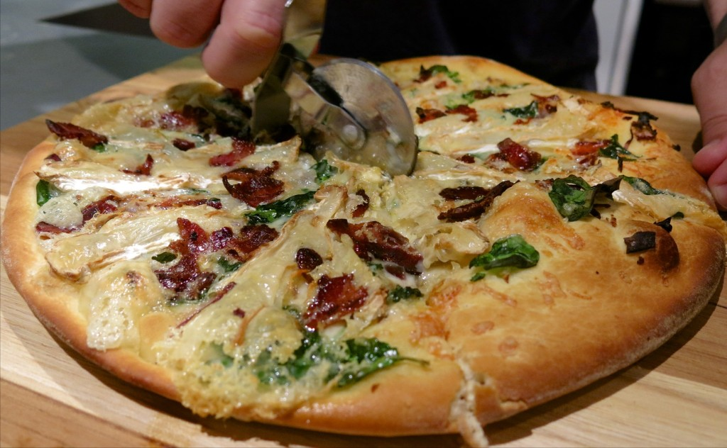 freshly baked pizza topped with camembert, bacon, red onion, garlic, spinach