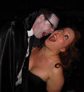 Dracula prepares to bite a woman on the neck