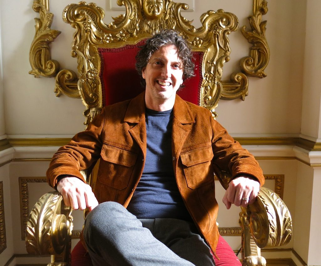 The Royals' creator Mark Schwahn sitting in a throne on the London set
