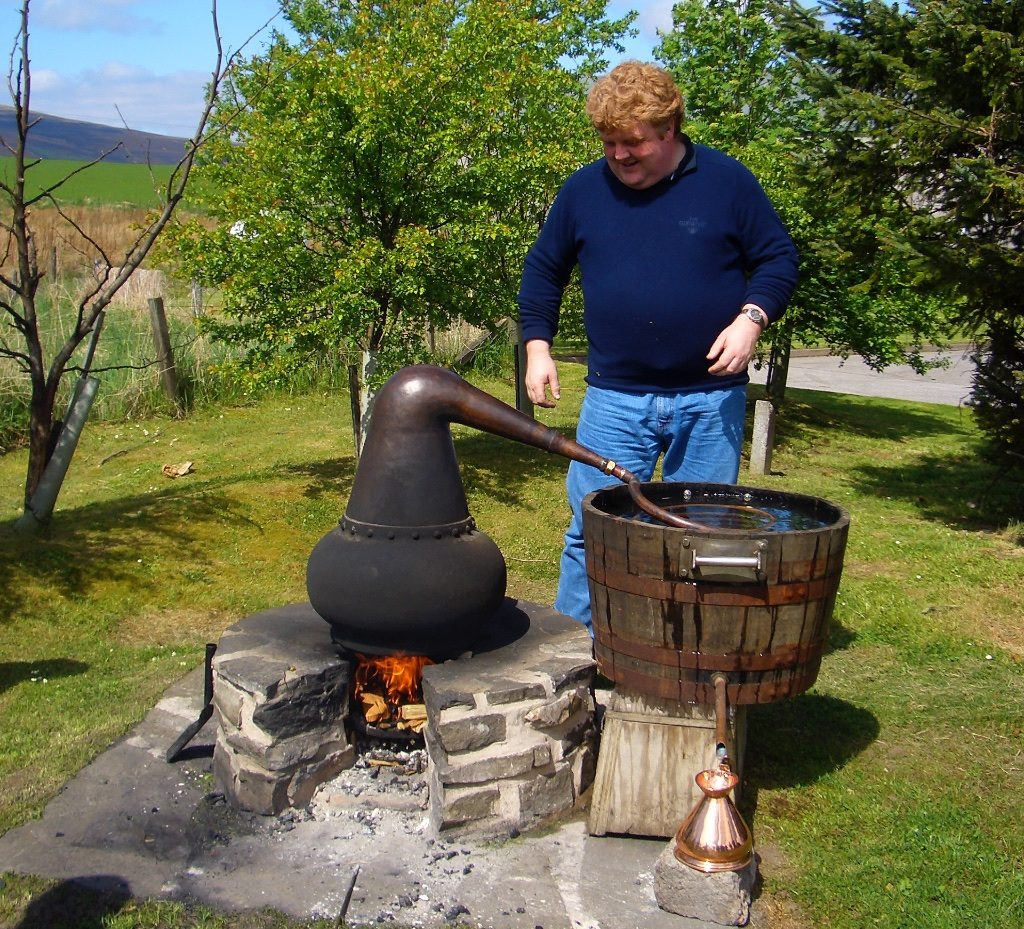 man distilling whisky at an outdoor still