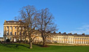 The Royal Crescent in Bath, England curves out across a green grassy lawn beneath a brilliant blue sky.