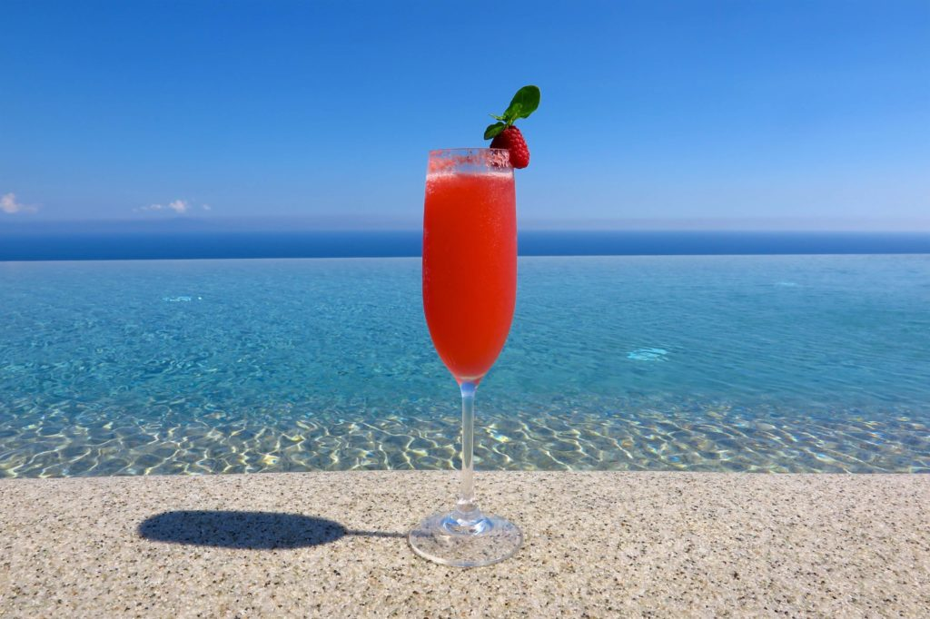fruity tropical cocktail by swimming pool