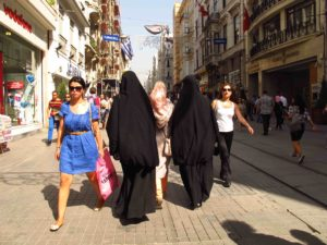 women in burkas and in Western dress on